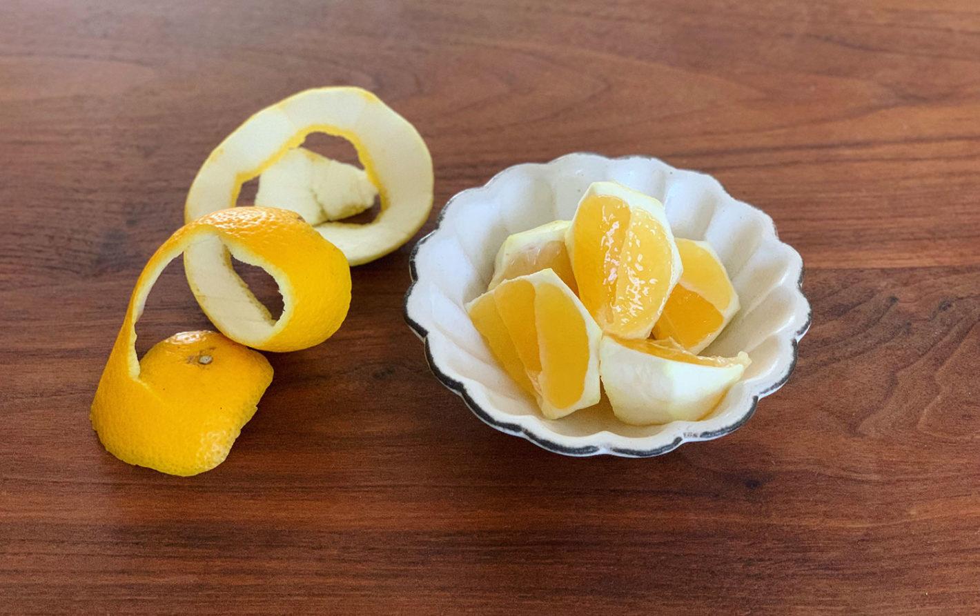 カットした小夏が白い小皿に盛られている。果肉も明るい黄色。りんごのようにくるくると向いた皮が横に置いてある。