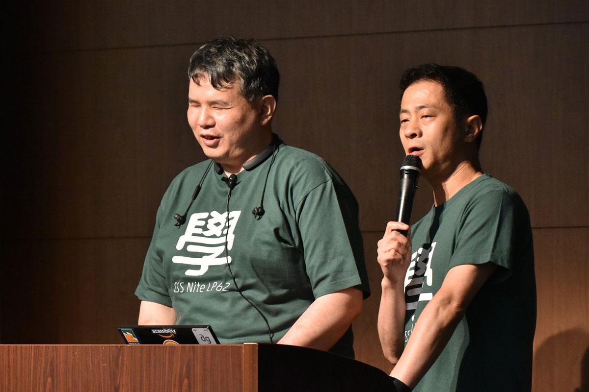 写真:目を閉じて微笑んでいる辻さんと、マイクを持ってお話中の植木さん。辻さんはピンマイクをつけて、イヤホンを肩から下げている