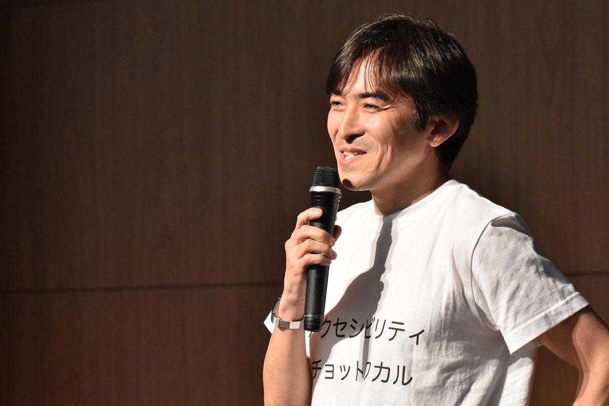 写真:笑顔でお話中の木達さん。Tシャツは白地に黒文字