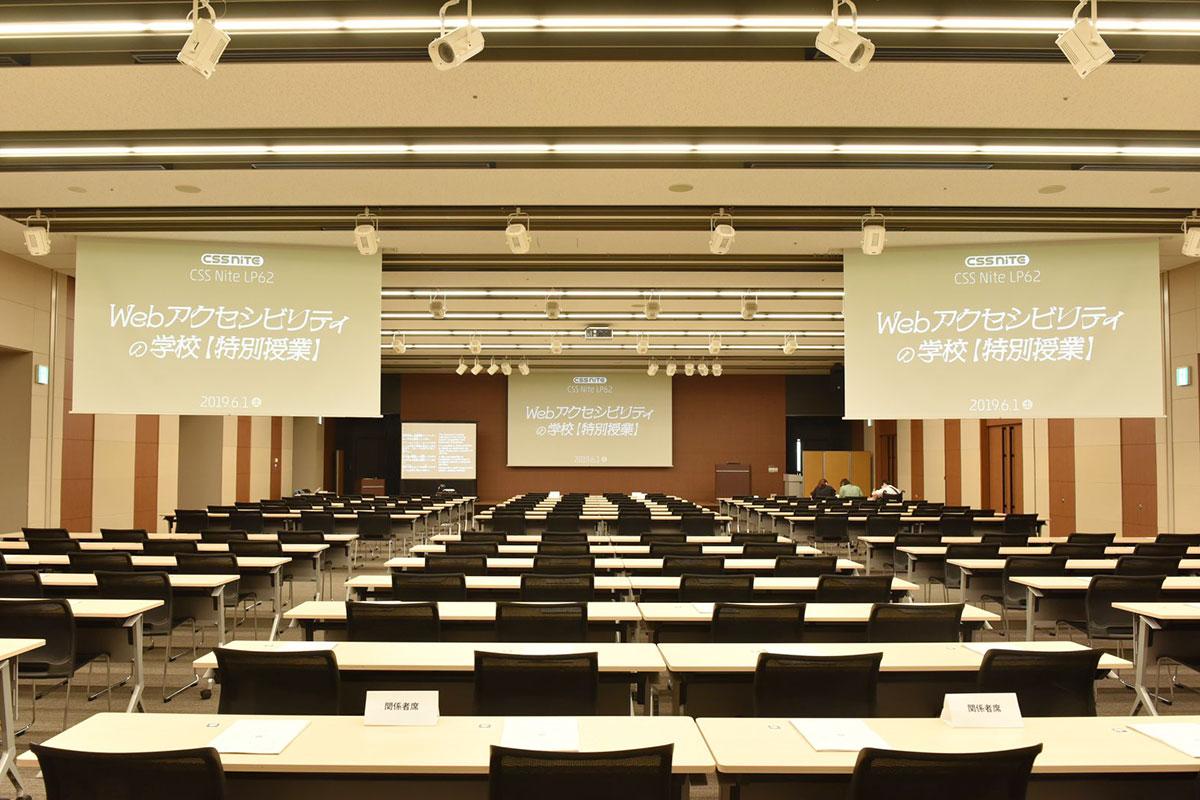 写真:整然と机と椅子が並んだ会場。前方中央と後方左右にはスライドを写すスクリーンがある。