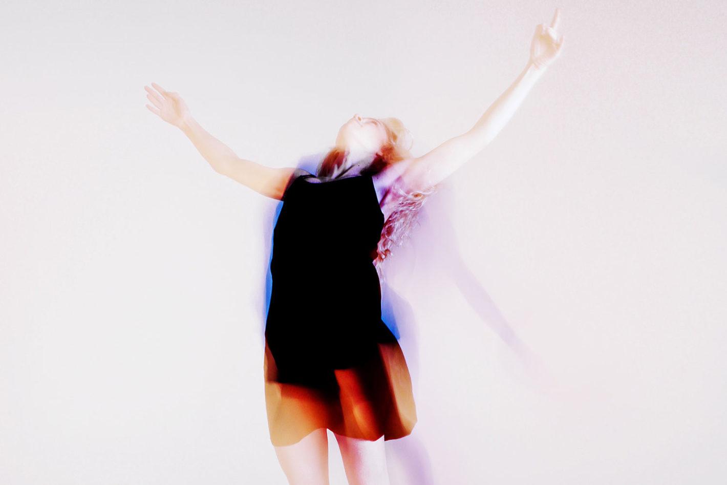 写真:両手を広げてジャンプするワンピースの女性